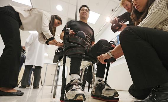 Роберт Ву примеряет экзоскелетное устройство для ходьбы, разработанное фирмой Ekso Bionics