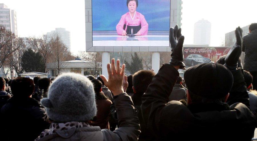 Северные корейцы смотрят трансляцию новостей навидеоэкране рядом сжелезнодорожным вокзалом вПхеньяне. Диктор зачитывает сообщение об испытании водородной бомбы. Среда, 6 января 2016 года. Фото— Kim Kwang Hyon, <i>AP</i>.