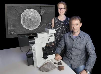 Члены научной группы  Университета Монаша нафоне фотографии космической сферулы.