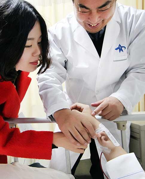 Доктор Го Шучжун осматривает ухо, выращенное наруке пациента.