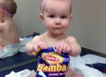 9—месячная девочка ест закуску с добавлением арахиса в кабинете педиатра.