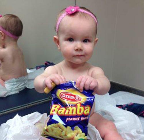 9—месячная девочка ест закуску сдобавлением арахиса вкабинете педиатра.