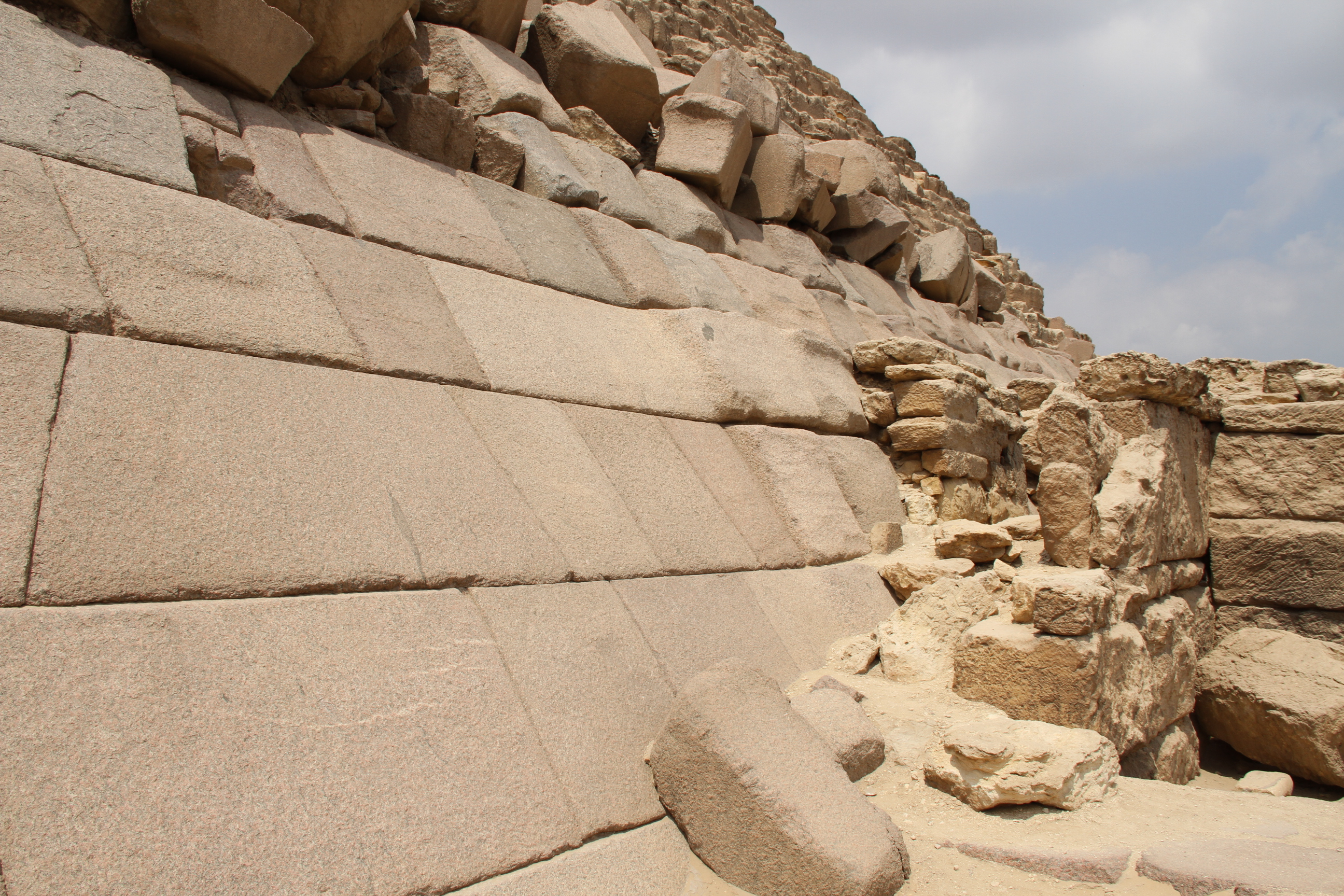 Гранитная облицовка пирамиды Менкаура. Видно, что поверхность блоков стали выравнивать, но незакончили