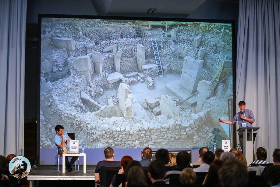 Максим Лебедев выступает, аудитория иведущий форума синтересом слушают.