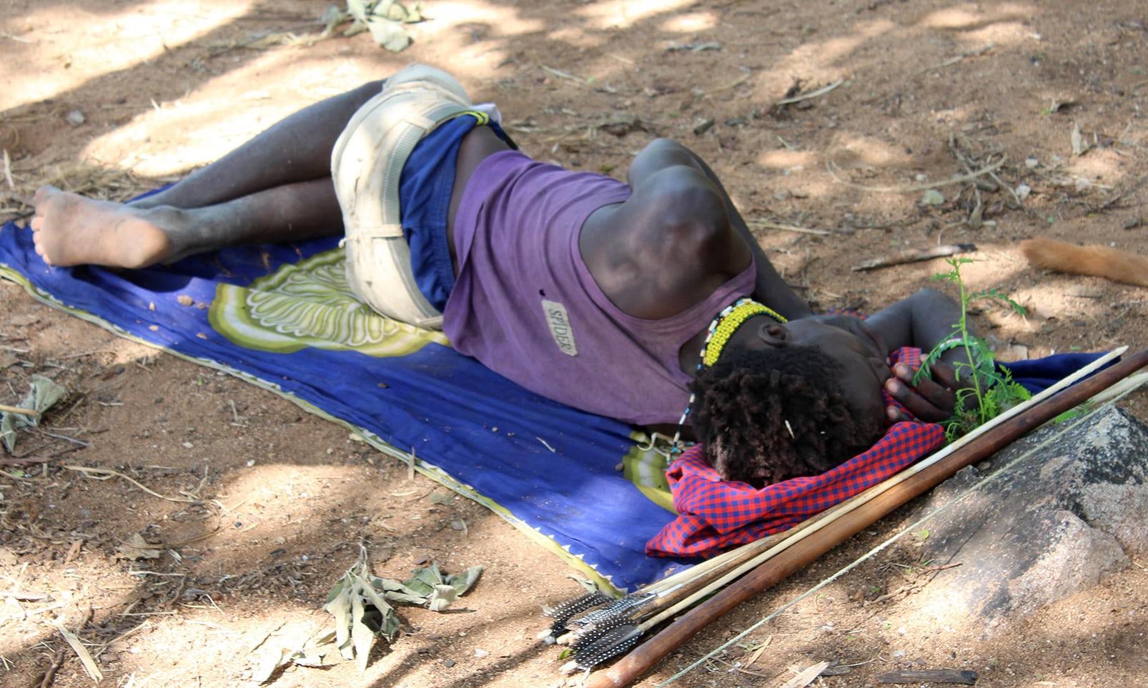 Член племени хадза отдыхает прямо наземле.
