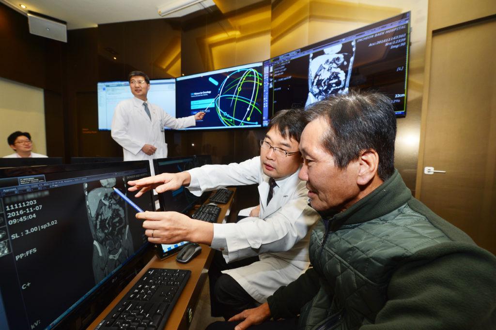 Чо Тхэ-Хён (справа), первый кореец, которому предстоит лечение спомощью Watson for Oncology, знакомится со своими медицинскими данными вприсутствии онкологов Медицинского центра Гиль при Университете Гачон