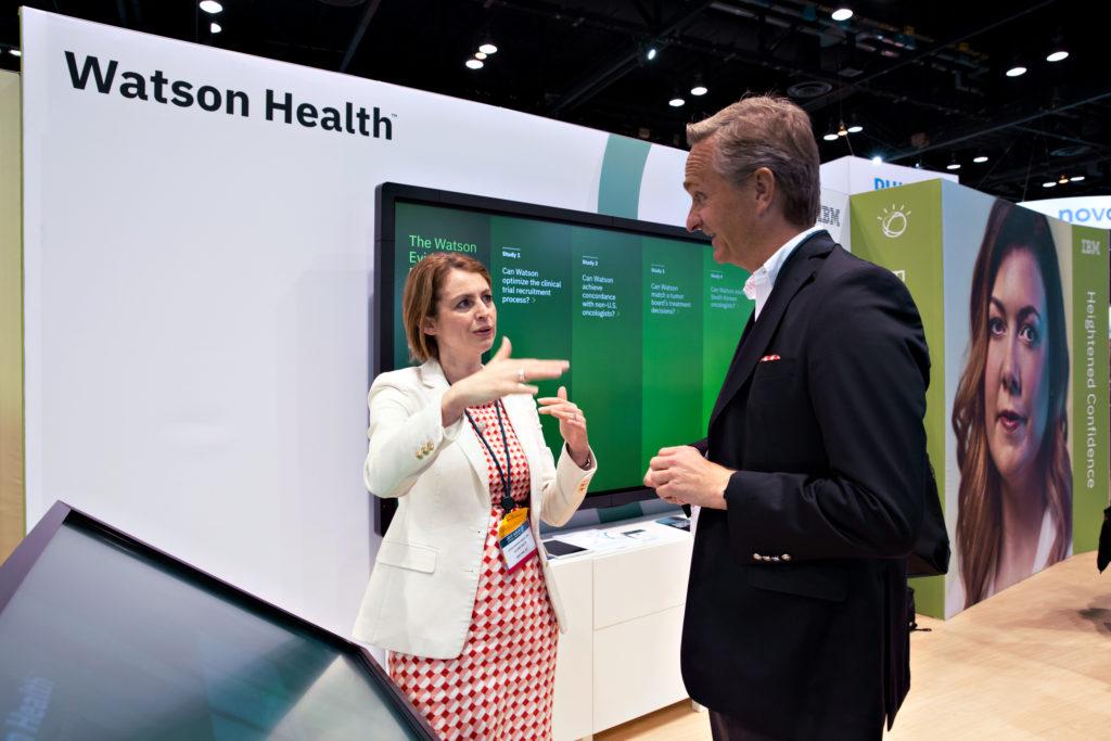 Луиза Робертс (Louisa Roberts) (слева), представляющая IBM Watson Health, беседует сруководителем отдела исследований иразработок Merck Оливером Машински (Oliver Maschinsky) устенда «Ватсона» наонкологической конференции ASCO 2017 года вЧикаго
