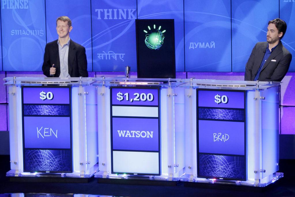 Чемпионы игры Jeopardy! Кен Дженнингс (Ken Jennings) (слева) иБрэд Раттер (Brad Rutter) наблюдают, как Watson опережает их вответе навопрос во время раунда в2011 году