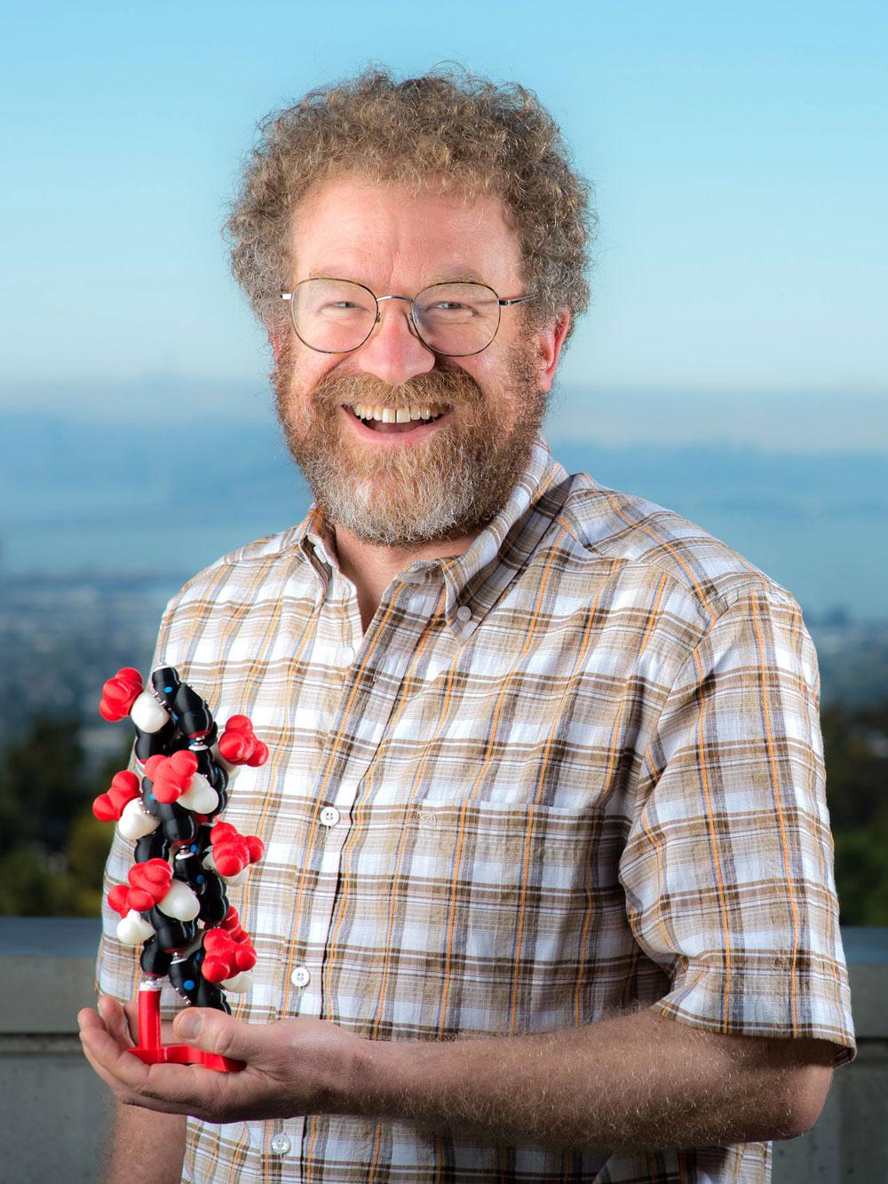Рональд Цукерман, химик Национальной лаборатории Лоуренса Беркли, демонстрирует модель одной из белковоподобных структур. Эта структура получена им наоснове искусственных полимеров, называемых пептоидами. Внастоящее время Цукерман применяет пептоиды для проверки предсказаний новой гипотезы происхождения жизни