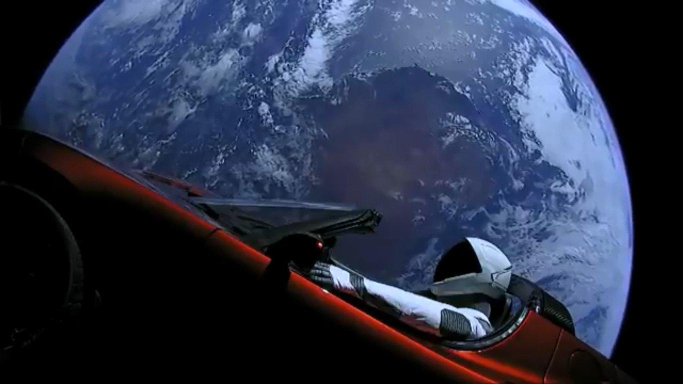 Манекен Starman вэкспериментальном скафандре SpaceX сидит вводительском сиденье вишнёвой Tesla Roadster наорбите Земли
