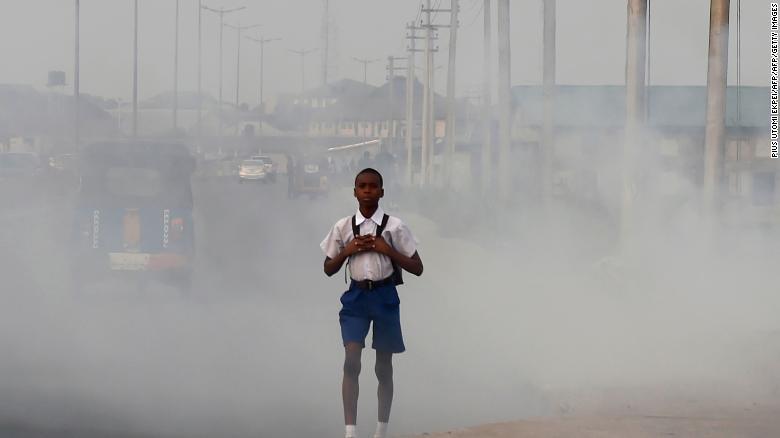 Как правило, чем беднее страна, тем больше загрязнена её атмосфера. Наснимке: нигерийский школьник прокладывает себе дорогу сквозь клубы дыма от нелегальных нефтеперерабатывающих заводов.