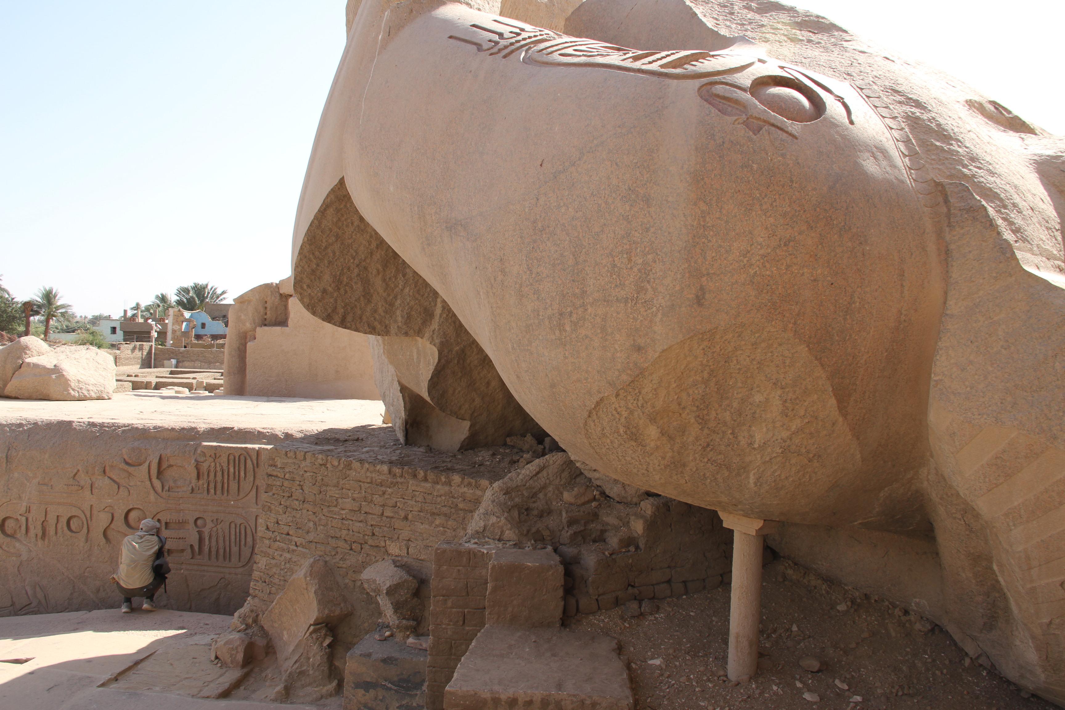 Гранитная статуя перед храмом Рамсеса II настолько велика, что непоместилась вкадр. Слева накорточках— Николай Васютин