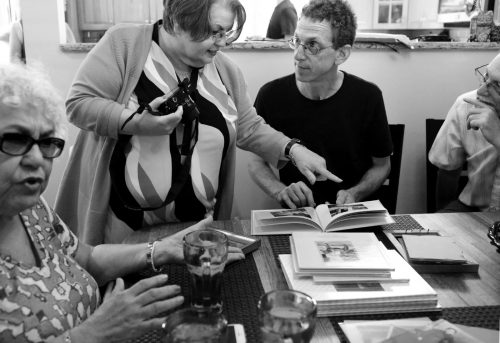 Филис Пуллман, слева, двоюродная сестра Элис Коллинз Плебух, иЭлис, которая беседуют со своими троюродными братьями Дэном Кляйном иДжерри Кляйном. Они просматривают фотоальбомы своих семей.
