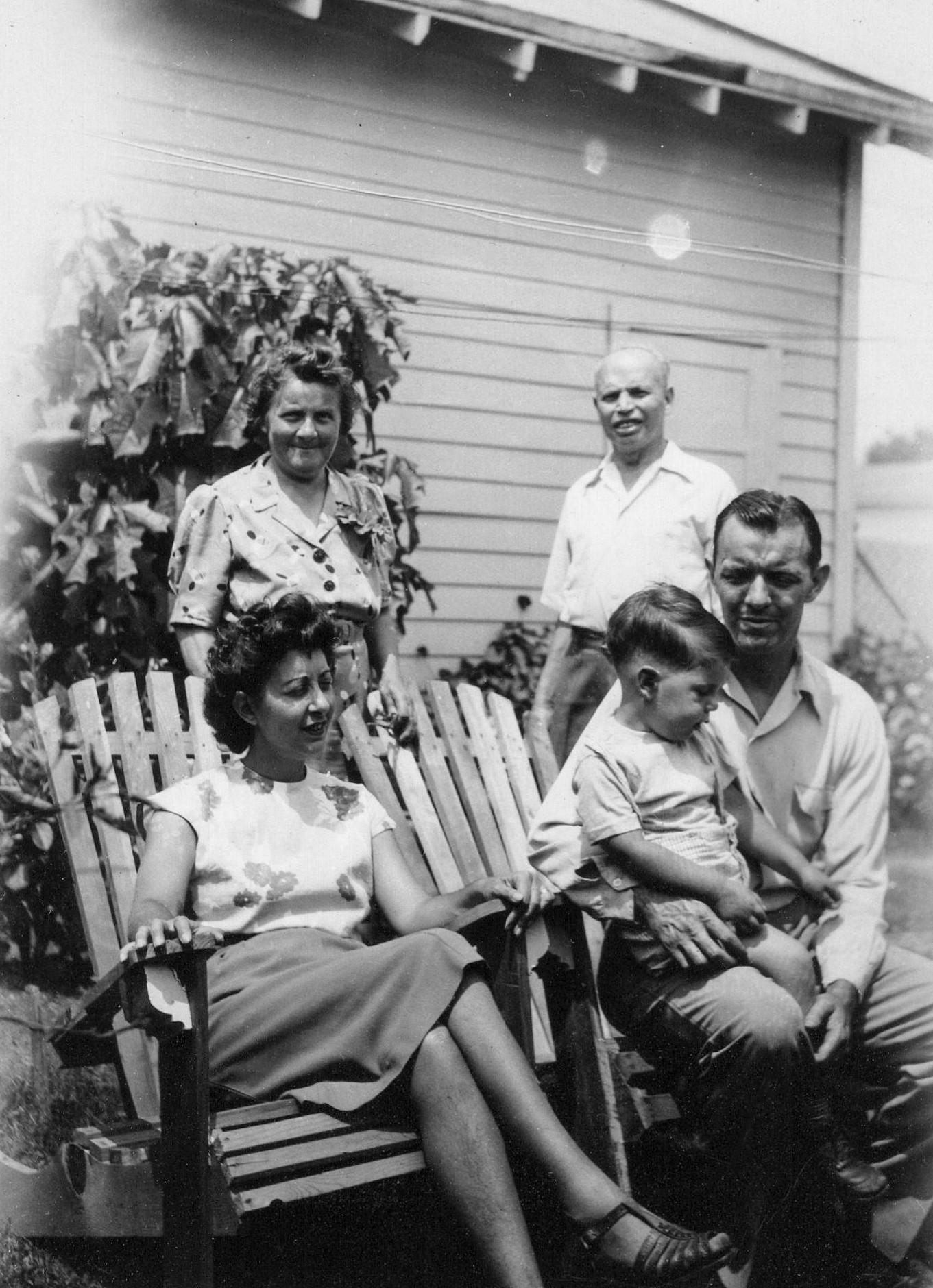 Сидят слева направо— первая жена Филлипа Бенсона, Эстер Аболафия Бенсон, их сын Кенни иФиллип Бенсон. За ними стоят Ида Котт Бенсон иСэм Бенсон, родители, скоторыми Филлип Бенсон воспитывался.