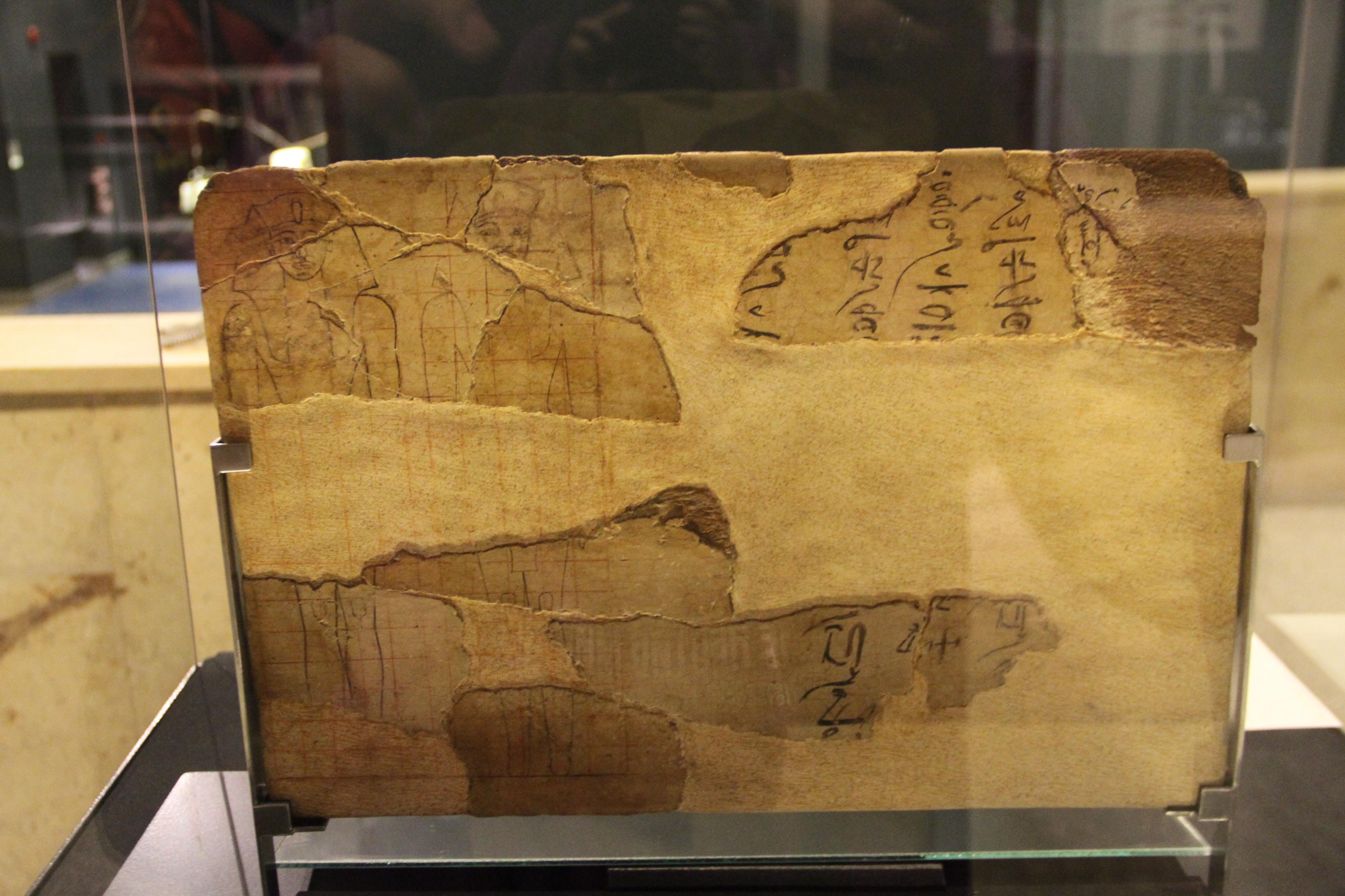 Фрагменты деревянной доски снаброском двух статуй.