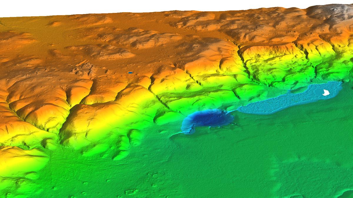 Изображение, полученное спомощью лидара, показывает расположение церемониального центра, занимавшего 2 километра вдоль известнякового хребта свидом налагуну Экнааб (белое пятно справа), место отбора проб для палеоэкологического исследования вГватемале.