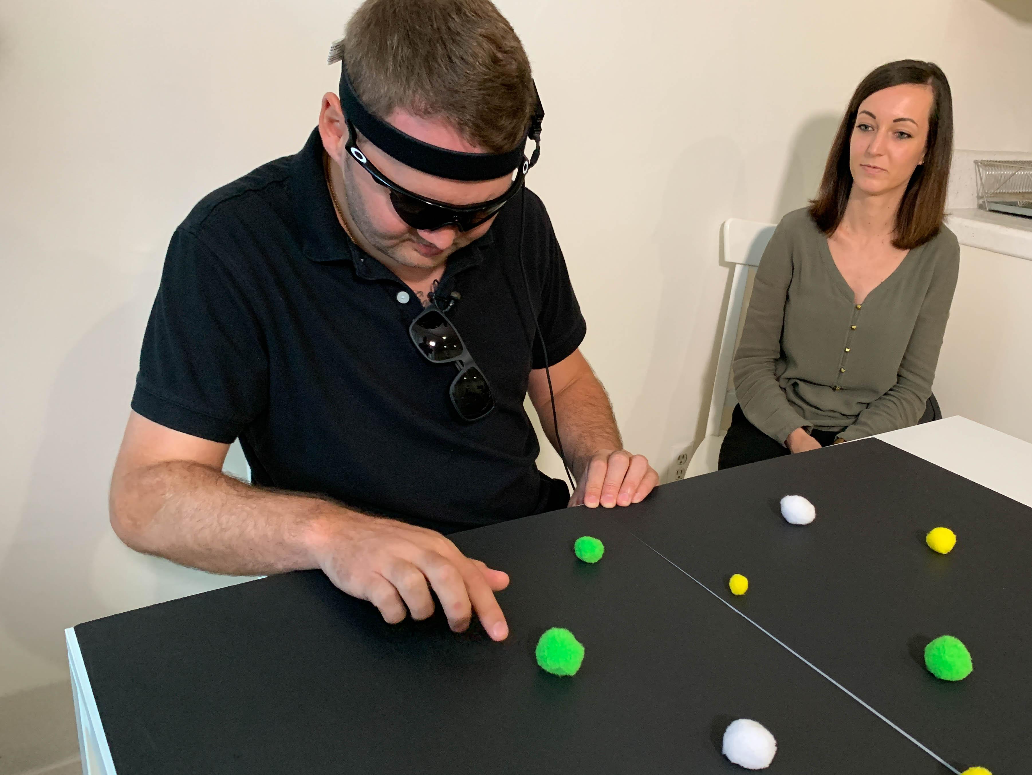 Джейсон Эстерхёйзен, потерявший зрение вавтокатастрофе, ищет предметы, рядом его жена Сумари. Видеокамера наочках передаёт сигналы устройству вего мозгу, позволяя отличать светлое от тёмного. Фото: UCLA Health.