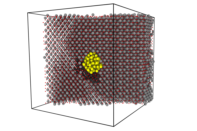 Пример расчётной ячейки: кристаллическая решётка диоксида урана (серый цвет— атомы урана уран, красный— кислорода), содержащая пузырь ксенона (жёлтые атомы). Чёрным цветом показаны атомы урана, вытесненные вмеждоузельные положения. Такой кластер междоузлий существенно ускоряет диффузию пузыря. Предоставлено авторами статьи.