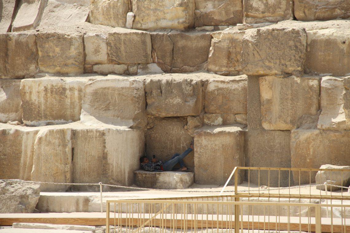 Cовременный египтянин занят своими делами уподножия пирамиды Хуфу