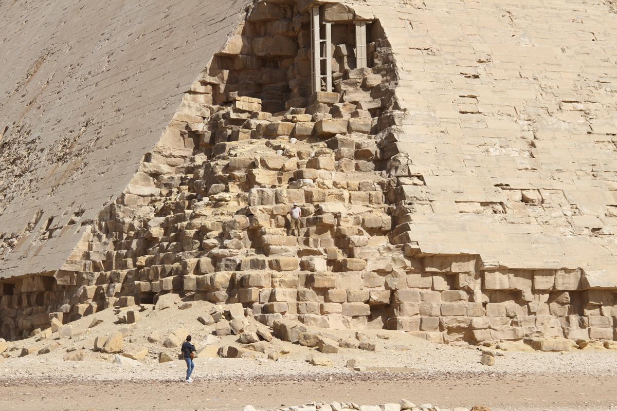 Русо (или украино) туристо позирует, забравшись на10-й ряд пирамиды