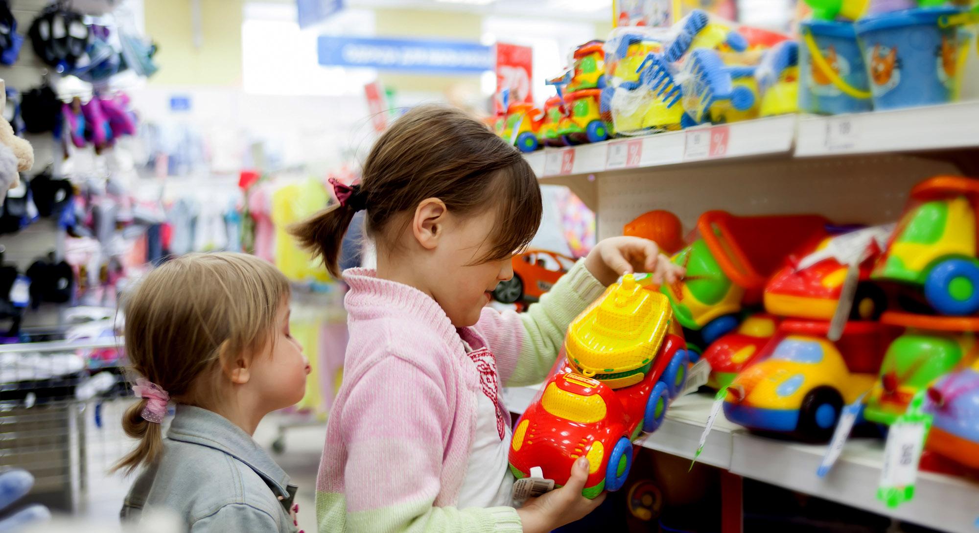 Девочки разглядывают вмагазине игрушечный автомобиль.